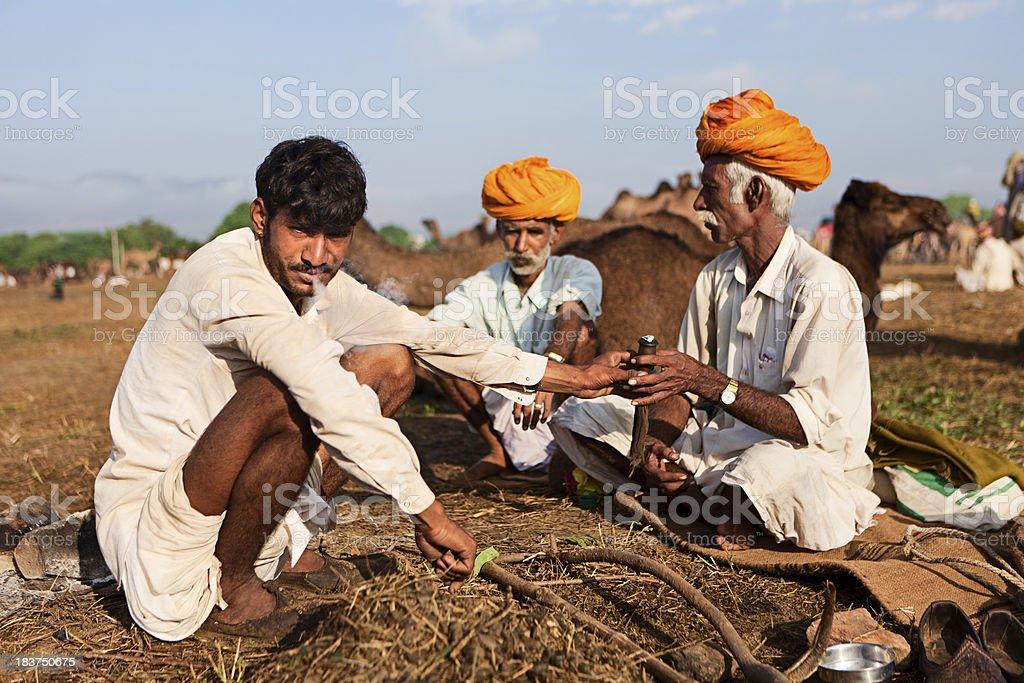 Indian men smoking the pipe during festival in Pushkar. stock photo