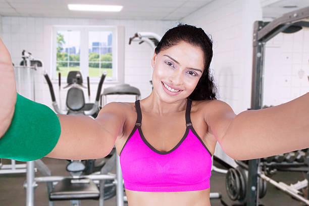 indian model makes selfie picture at gym - call center stockfoto's en -beelden