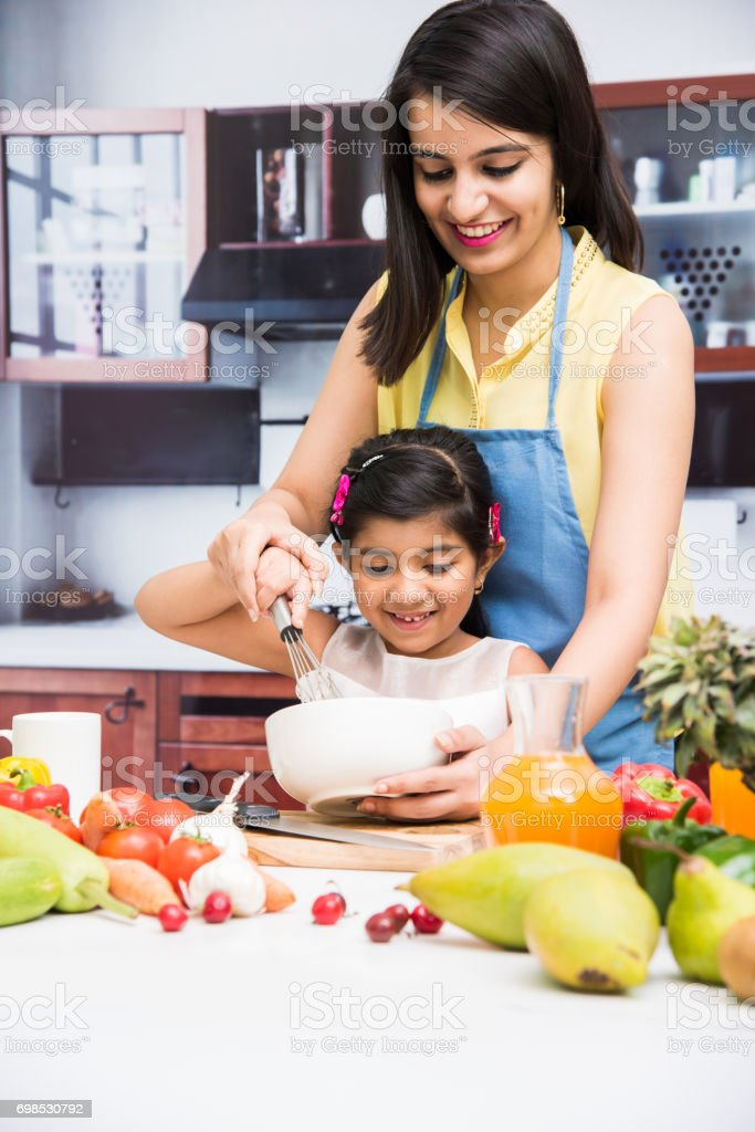 indian mother and child in kitchen stock photo
