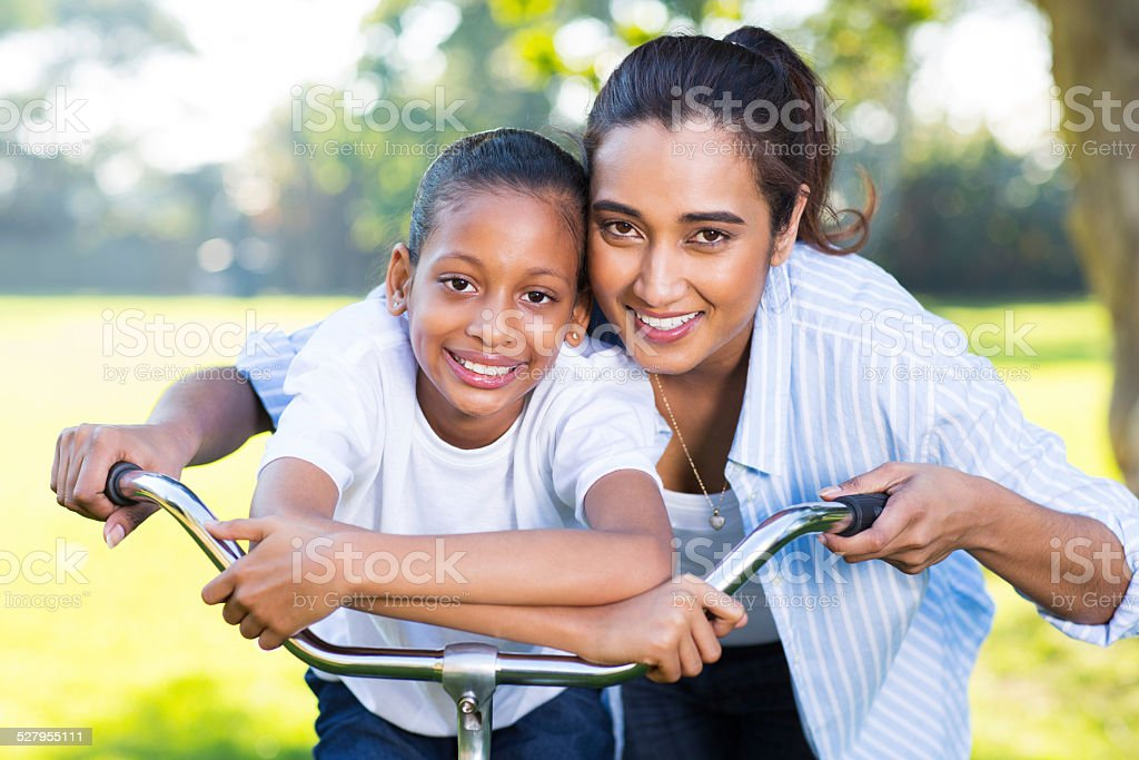 indian mother and her daughter outdoors on a bike stock photo