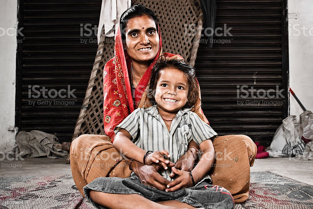 Indian Mother Together With Her Young Daughter Real People: Happy smiling indian mother together with her young daughter sitting on carpet in their home. Real People of New Delhi, India. Edited Colors. Portrait. 30-39 Years Stock Photo