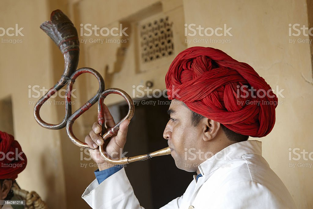 Indian musician playing curved trumpet type wind instrument stock photo
