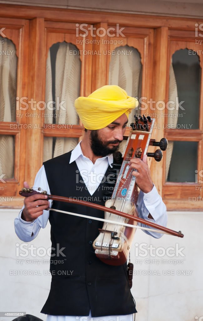 Indian musician playing sarangi in Golden Temple stock photo