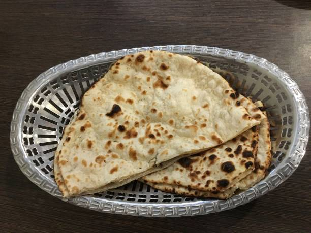 Indian naan bread basket Indian naan bread cut in half in a metal basket naan bread stock pictures, royalty-free photos & images