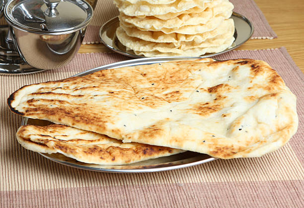 Indian Naan Bread Indian naan flatbreads on serving tray naan bread stock pictures, royalty-free photos & images