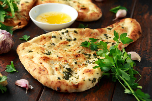 Indian naan bread with garlic butter on wooden table Indian naan bread with garlic butter on wooden table. naan bread stock pictures, royalty-free photos & images
