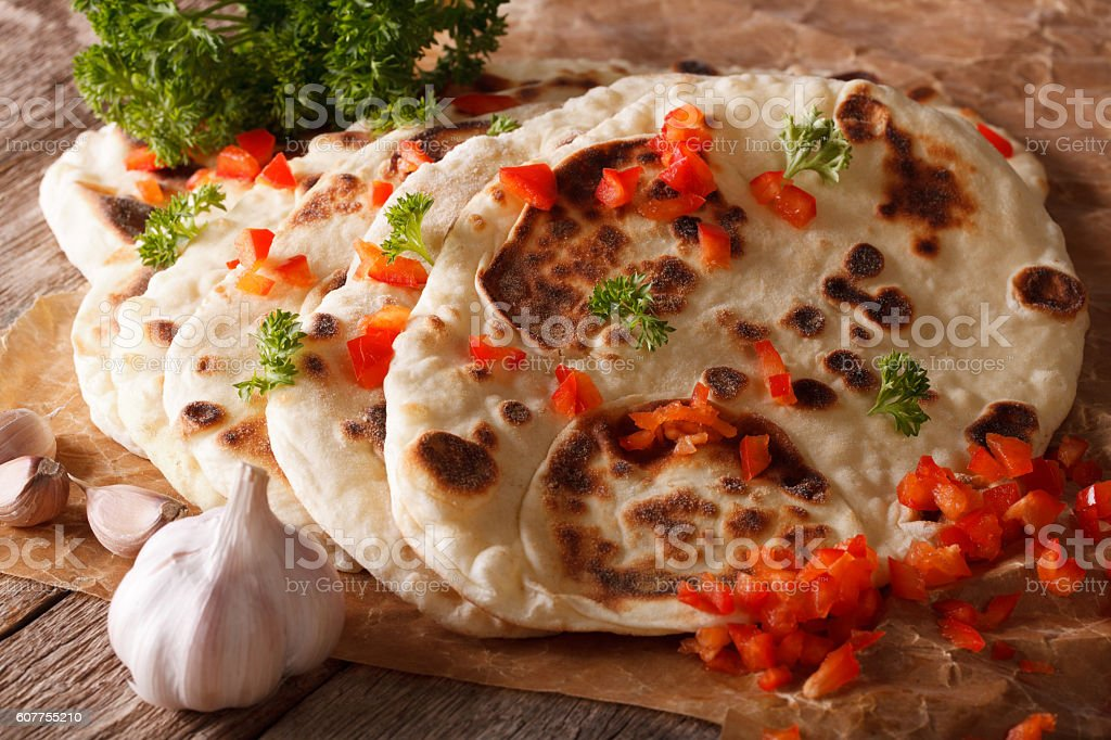 Indian Naan flat bread with garlic and pepper macro. horizontal stock photo