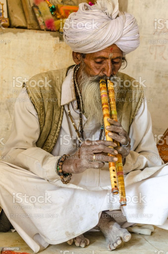 Indian Old man playing two flutes royalty-free stock photo