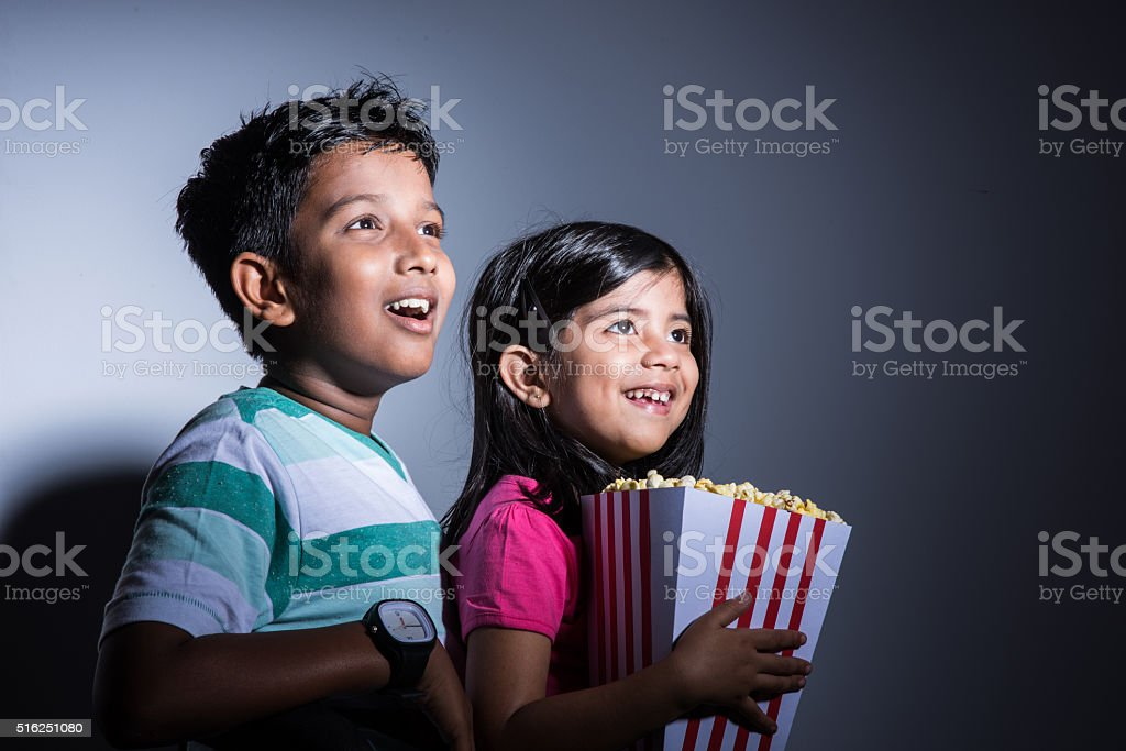 indian or asian cute girl and boy eating popcorn stock photo
