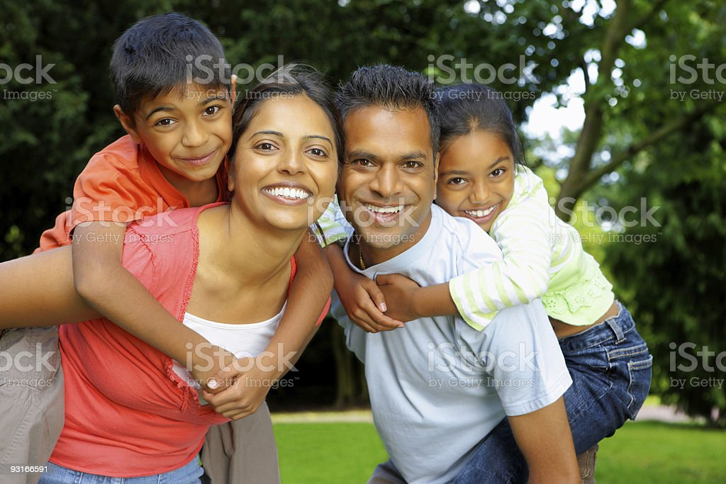 Indian parents giving piggyback ride to their children outdoors stock photo