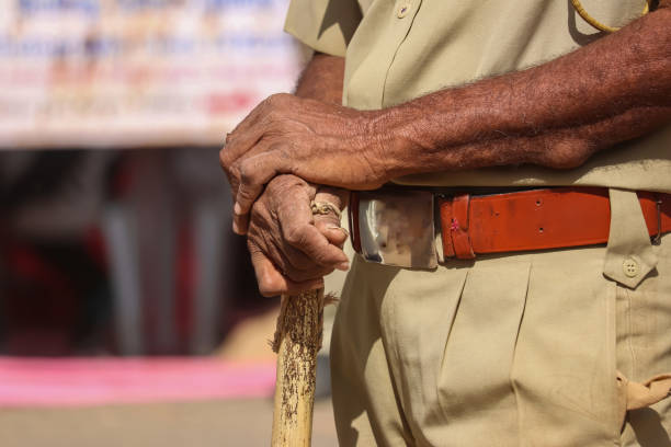 Indian policeman close to Police stick and uniform,  Indian policeman (CRPF) with bamboo sticks patrols, selective focus, Hand in hand police man view Indian policeman close to Police stick and uniform,  Indian policeman (CRPF) with bamboo sticks patrols, selective focus, Hand in hand police man view police uniform stock pictures, royalty-free photos & images