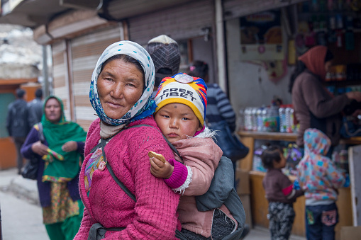 Leh, India - june 21, 2015 : Indian poor local woman with the child on the street market in mountain village Leh, Ladakh region, north India, close up. Poverty is a major issue in India