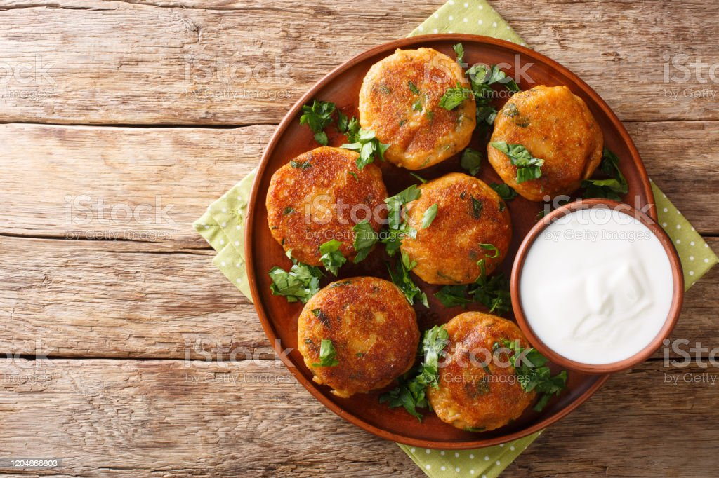 Indian potato patties Aloo Tikki served with yogurt close up in a dish. Horizontal top view Indian potato patties Aloo Tikki served with yogurt close up in a dish on the table. Horizontal top view from above Above Stock Photo