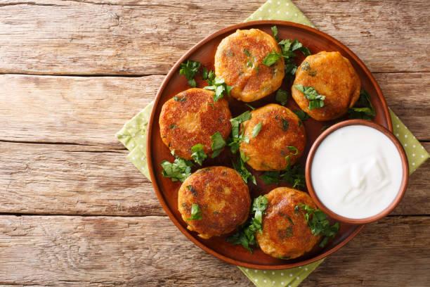 Indian potato patties Aloo Tikki served with yogurt close up in a dish. Horizontal top view stock photo