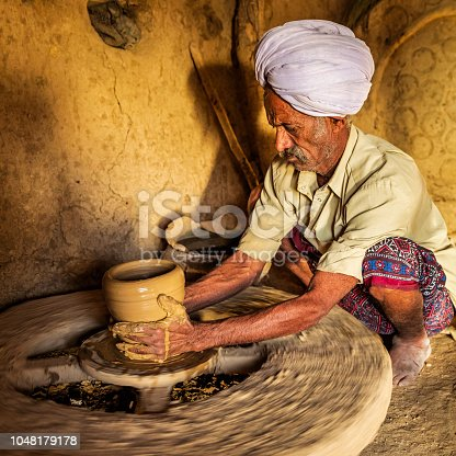 Indian potter working in his workshop, desert village in Rajasthan, India
