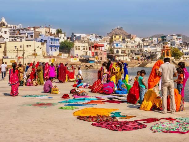 Indian religious pilgrims wearing beautiful, colorful clothing are gathered beside Pushkar Lake in Rajasthan, North India. stock photo