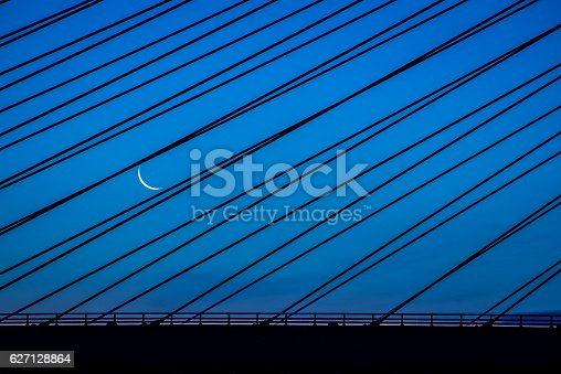 The moon comes up during twilight over the Indian River Inlet Bridge in Delaware