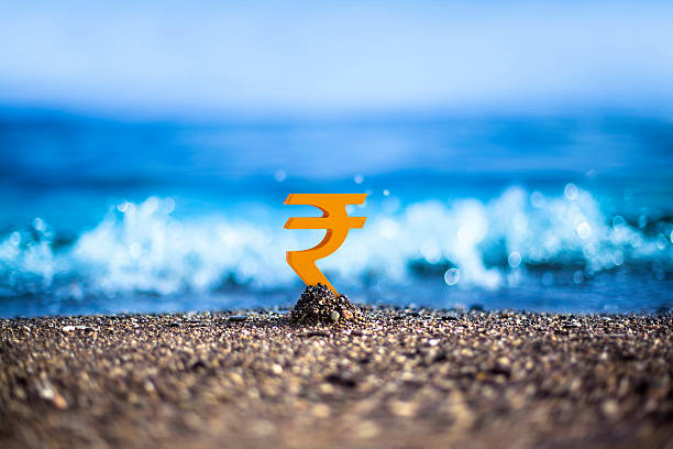 Indian Rupee is standing on the wavy sea side stock photo