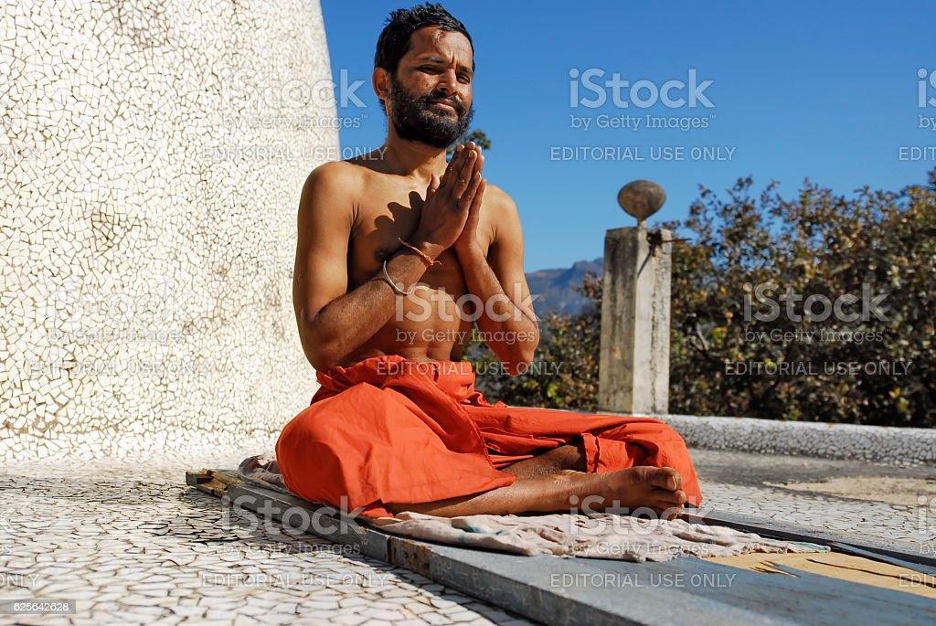 Indian sadhu does exercises of yoga, Maharishi Ashram, Rishikesh, India. stock photo