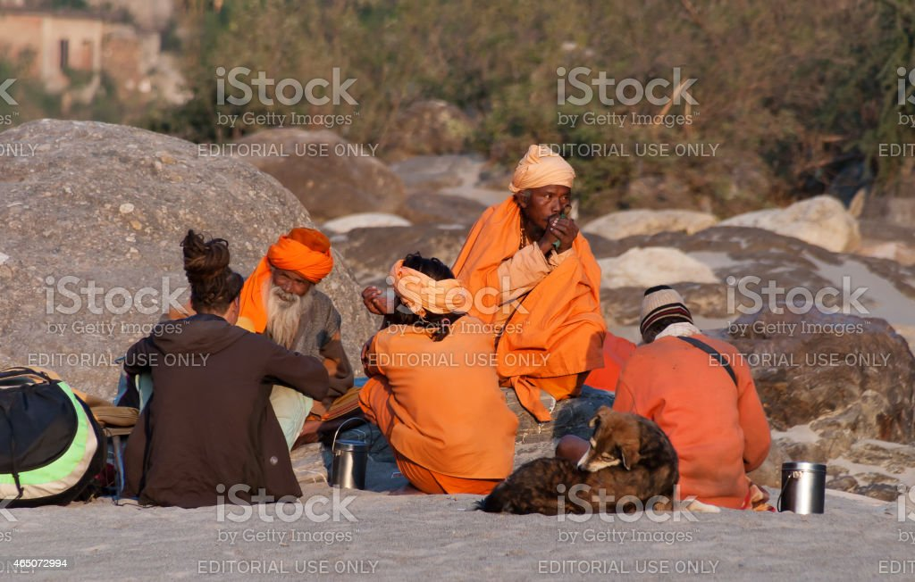 Indian sadhus siting on the beach near River Ganga stock photo