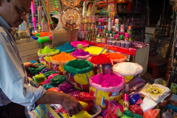 Indian Salesman in front of his shop selling colorful powder for Holi Festival, Jaipur, Rajasthan, India stock photo