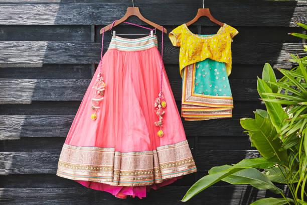 indische sari (sari) hochzeitskleid und bluse an der hölzernen wand hängen - pailletten shirt stock-fotos und bilder
