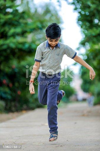 Indian school boy playing hop-scotch in playground