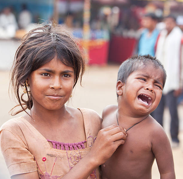 Indian siblings beautiful girl carries crying baby brother. stock photo