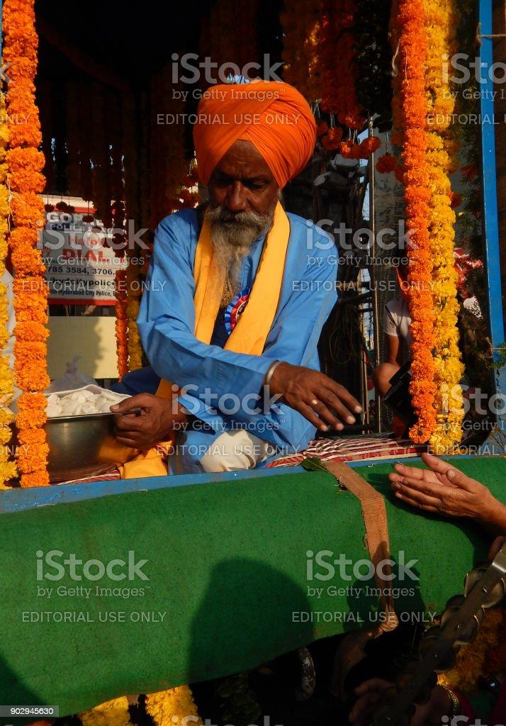 Indian Sikh man on float with Guru Granth Sahib,in Nagar Keertan on birthday of Guru Nanak Dev,distributes prasad to people stock photo