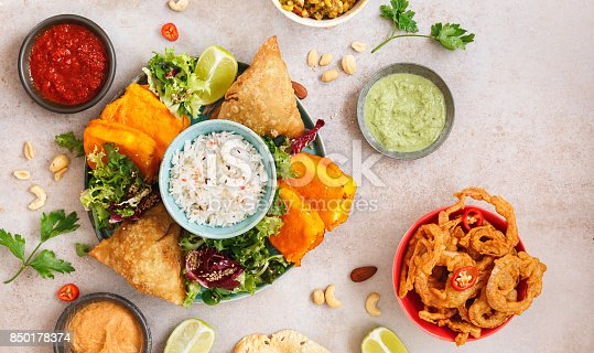 Assorted Indian snacks with rice, salad and sauces on rustic surface. Top view, blank space