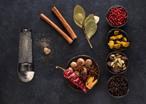 Indian spices and herbs in bowls on a black concrete background, top view, flat lay Indian spices and herbs in bowls on a black concrete background, top view, flat lay garam masala stock pictures, royalty-free photos & images
