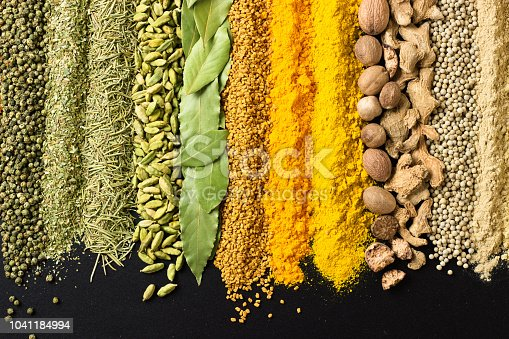 Colorful spice background for website  headers or food labels. Collection of herbs and herbs are scattered on black table.