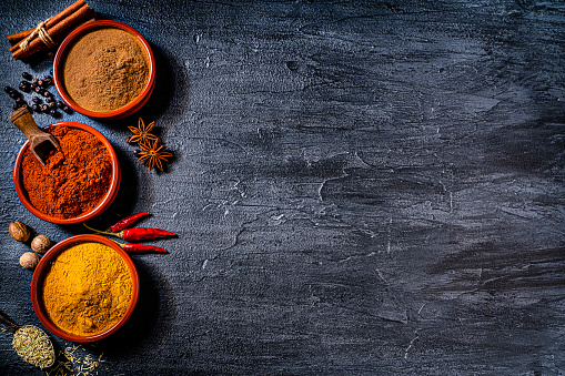 Indian spices background: top view of three bowls filled with cinnamon powder, paprika and turmeric shot on dark slate table. Cinnamon sticks, star anise, nutmeg, dried chili peppers, dried oregano and peppercorns are all around the bowl. Predominant colors are black, red and yellow. The composition is at the left of an horizontal frame leaving useful copy space for text and/or logo at the right. High resolution 42Mp studio digital capture taken with SONY A7rII and Zeiss Batis 40mm F2.0 CF lens