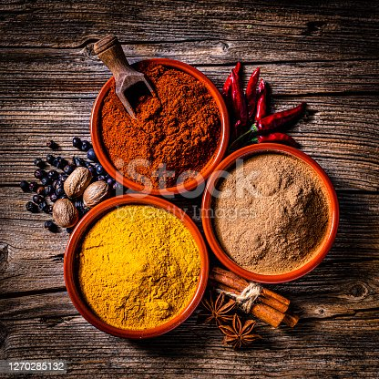 Indian spices background: top view of three bowls filled with cinnamon powder, paprika and turmeric shot on rustic wooden table. Cinnamon sticks, star anise, nutmeg, dried chili peppers and peppercorns are all around the bowl. Predominant colors are brown, red and yellow. High resolution 42Mp studio digital capture taken with SONY A7rII and Zeiss Batis 40mm F2.0 CF lens