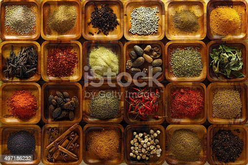 A large selection of commonly used Indian cooking spices in wooden trays on an old table. Spices include, chili ,cumin, tumeric, corriander, cumin, cardamon, garam masala, saffron, cinamon and star anise, poppy seed, sesame, cloves, nutmeg, black and white pepper corns, aniseed and fenugreek.