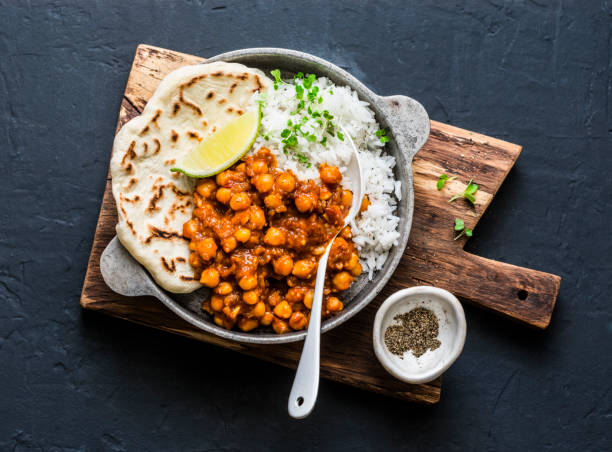 Indian spicy chickpeas curry with rice and naan bread in pan on dark background, top view. Healthy tasty vegetarian food Indian spicy chickpeas curry with rice and naan bread in pan on dark background, top view. Healthy tasty vegetarian food chick pea stock pictures, royalty-free photos & images