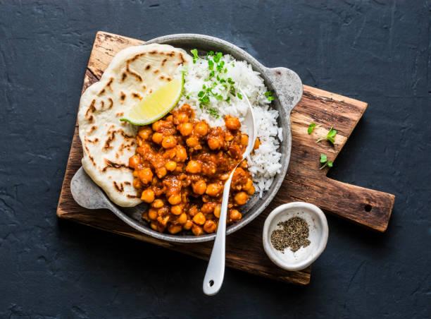 Indische würzige Kichererbsen curry mit Reis und Naan Brot in Pfanne auf dunklem Hintergrund, Ansicht von oben. Gesunde leckere vegetarische Kost – Foto