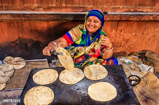 Indian street vendor preparing food - chapatti, flat bread, Jaipur - The Pink City, Rajasthan, India.  Jaipur is known as the Pink City, because of the color of the stone exclusively used for the construction of all the structures.