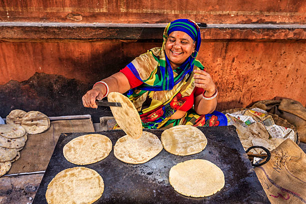 Indian street vendor preparing food - chapatti, flat bread Indian street vendor preparing food - chapatti, flat bread, Jaipur - The Pink City, Rajasthan, India.  Jaipur is known as the Pink City, because of the color of the stone exclusively used for the construction of all the structures. market vendor stock pictures, royalty-free photos & images