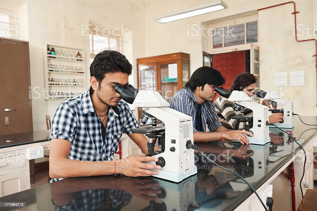 Indian Students Using Microscope In Science Laboratory. stock photo