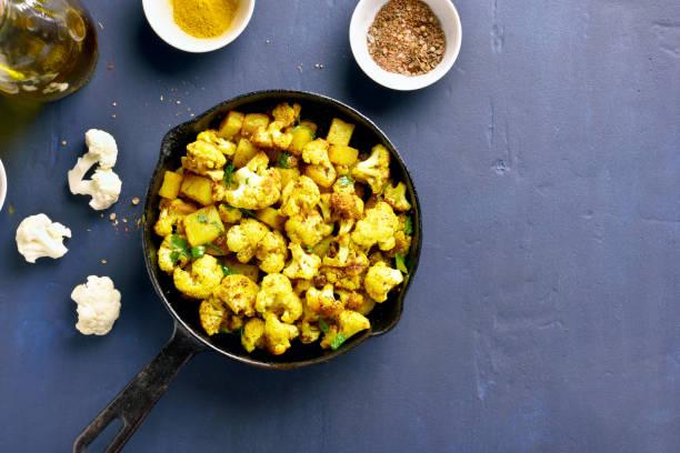 indisch blumenkohl mit kartoffeln - gebackener blumenkohl stock-fotos und bilder