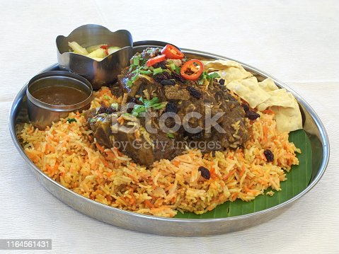 Indian style lamb biryani, with lamb, rice, peppers, herbs, pickled vegetables, and housemade sauce.