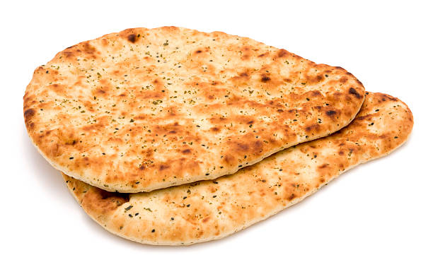 Indian style naan bread on a white background Indian style naan bread isolated on a white background. Naan bread is commonly eaten alongside curry. naan bread stock pictures, royalty-free photos & images