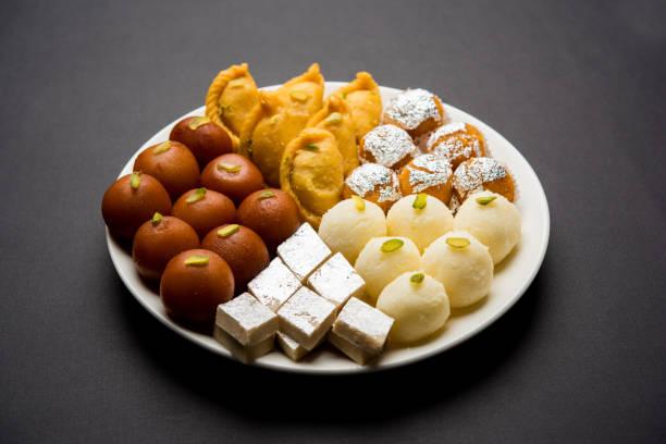 indian sweets in a plate includes gulab jamun, rasgulla, kaju katli, morichoor / bundi laddu, gujiya or karanji for diwali celebration - sweet food stock pictures, royalty-free photos & images