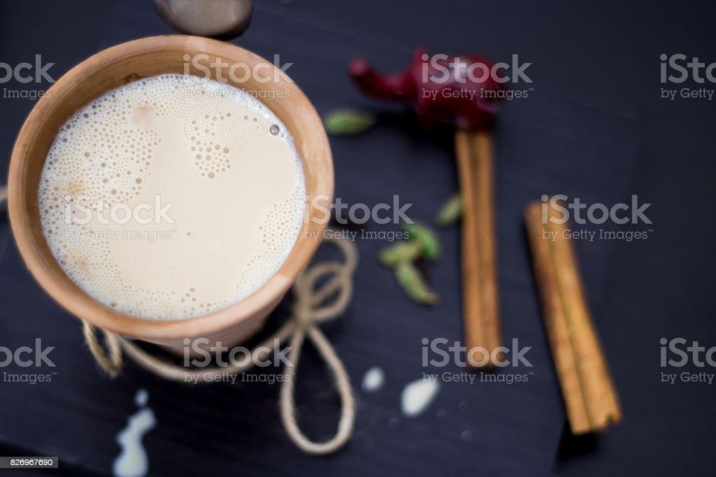 Thé Inde chai masala karak aux épices et le lait dans un verre d'argile sur un fond en bois - Photo