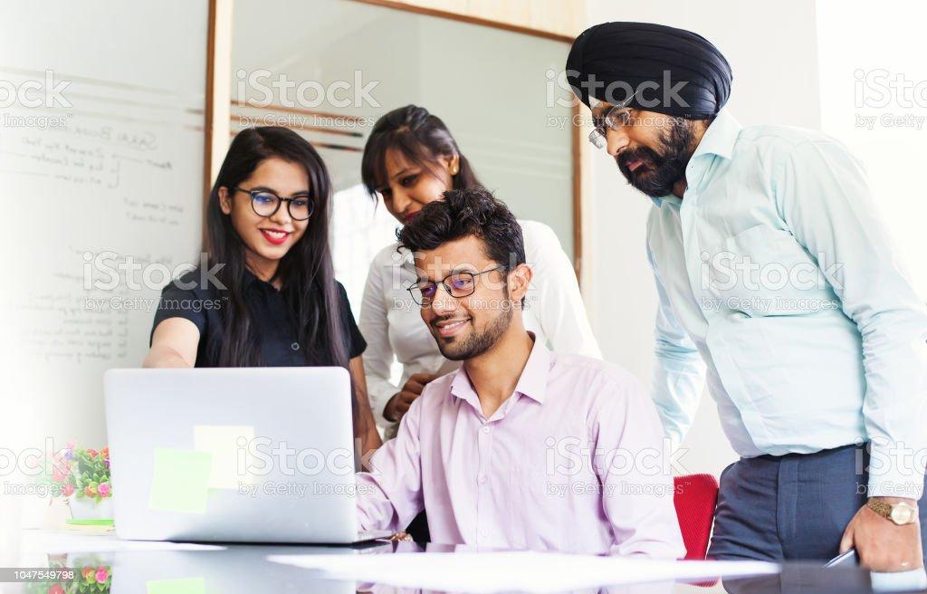 Indische Team zusammenarbeiten und auf der Suche auf einem Laptop-Bildschirm – Foto