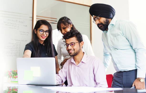 indian team working together and looking on a screen of laptop - индия стоковые фото и изображения