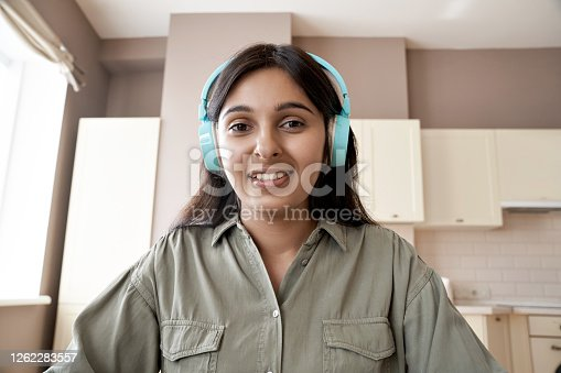 Indian teen girl college student teacher wearing headphones looking at web cam distance learn or teach online. Web lesson video call remote class, online job interview concept. Headshot. Webcam view.