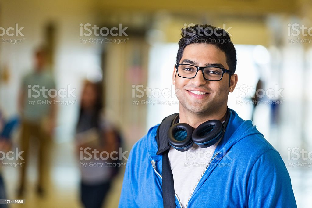 Indian teen student smiling in hallway of modern high school - Stock image .