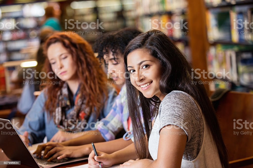 Indian teen studying in library with college age friends圖像檔